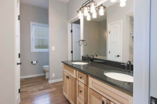 bathroom with double sink vanity and large mirror