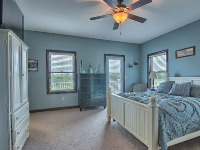 blue painted bedroom with bed and ceiling fan overhead