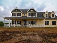 front of custom home with large windows, beige vinyl siding, wrap around porch