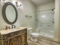 bathroom with large round mirror, white bathtub